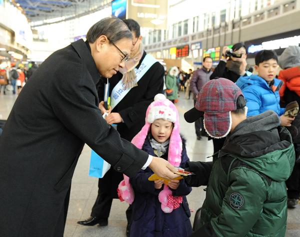 국민권익위원회 박재영 사무처장이 8일 오후 서울역 대합실에서 설 귀성객들에게 110.국민신문고 책자를 나눠주며 홍보를 하고 있다.